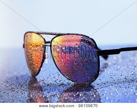 Wet sunglasses on a wet reflective surface.