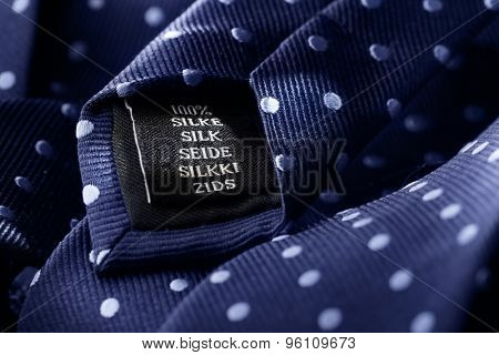 Label of a tie made of silk. Short depth of field, the sharpness is in the word Silk.