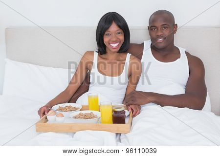 Portrait of a pretty couple taking breakfast in bed together at home in bedroom
