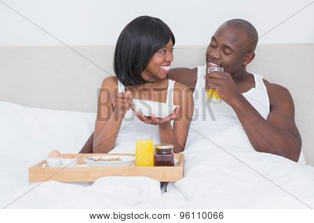 Pretty couple taking breakfast in bed together at home in bedroom