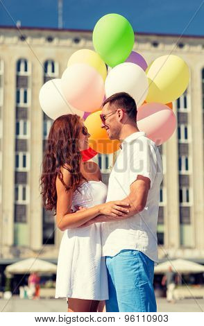 love, wedding, summer, dating and people concept - smiling couple wearing sunglasses with balloons hugging in city
