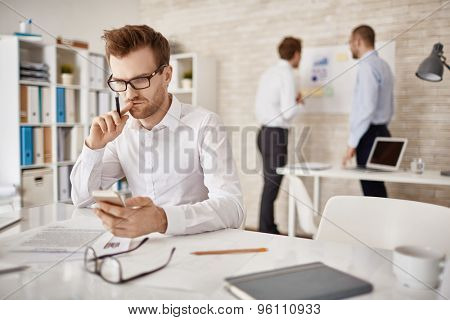 Serious businessman writing or reading sms in working environment