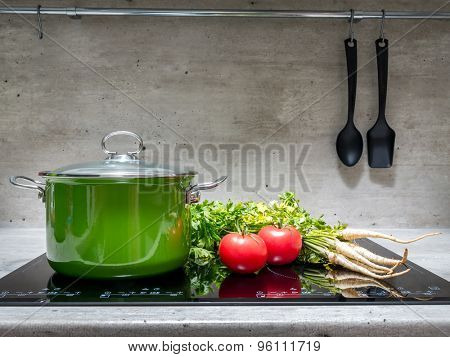 Green enamel stewpot with parsley and two tomatoes on black induction cooker