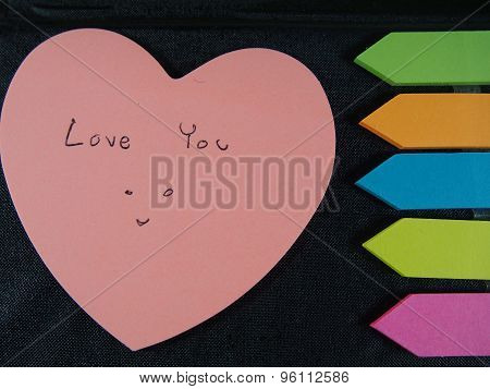 Love You With Smiling Face, Drawing And Writing On Pose Its Paper With Colorful Heart And Arrow On B
