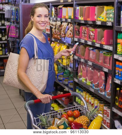 Pretty woman using her smartphone in front of product aisle at supermarket