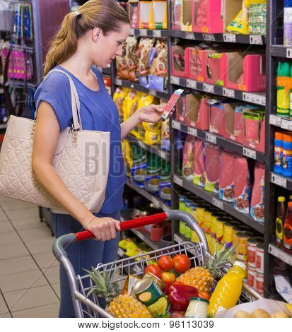 Pretty woman using her smartphone in front of product on shelf at supermarket