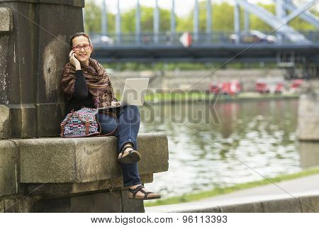 Young woman freelancer sitting on the stone embankment of the river with a laptop and talking on the phone.