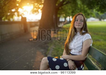 Beautiful young long haired girl sitting in a Park during golden sunset.