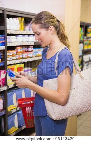 Pretty woman picking box in shelf in supermarket