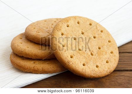Stack Of Sweetmeal Digestive Biscuits On Dark Wood And Napkin.