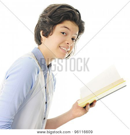 An attractive teen girl smiling at the viewer with the opened book she's been reading still in her hand.  On a white background.