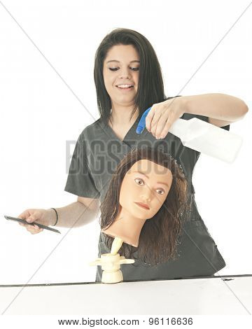 An attractive student cosmetologist happily spraying her practice head with water.  On a white background.