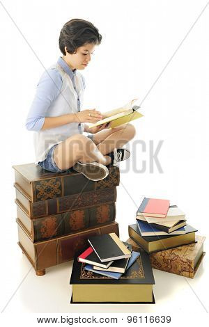 An attractive young teen reading a book on a stack of huge books with others scattered on the floor around her.  On a whitet background.