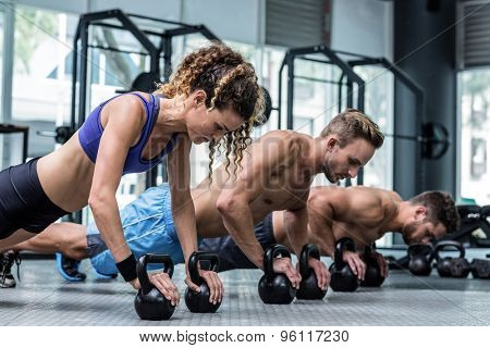 Three muscular athletes on a plank position with kettlebells