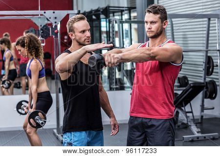 Trainer supervising a muscular man lifting a kettlebell