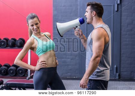 Trainer yelling through the megaphone to a muscular woman
