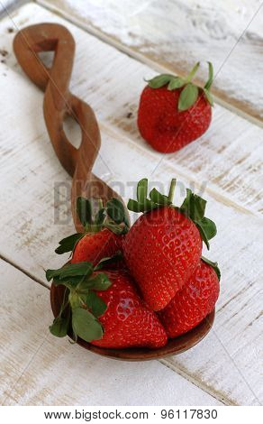 Large strawberries on a wooden spoon