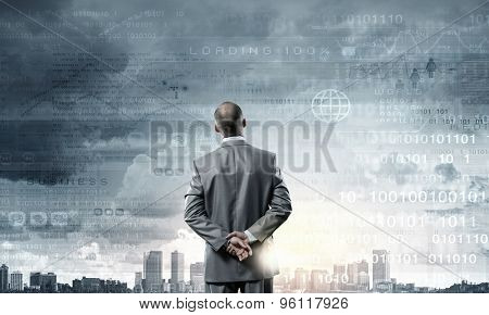 Businessman stands back and looks at flying objects