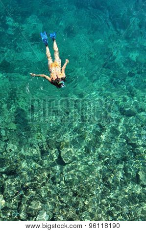 Young Lady Snorkeling Over Coral Reefs