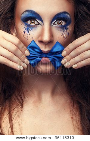 Woman With Fashion Make Up And Bow In Mouth