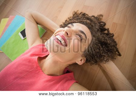 Smiling young creative businesswoman lying on the ground