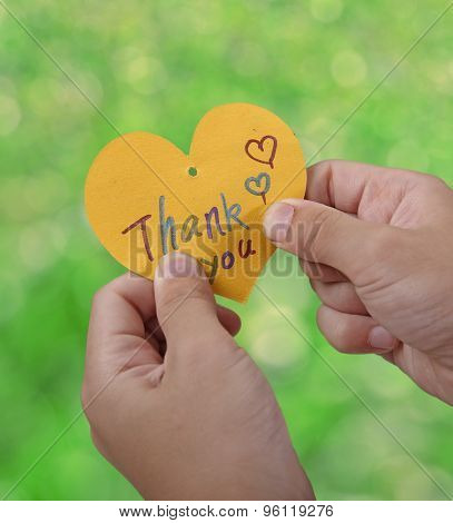 Child holding a thank you card