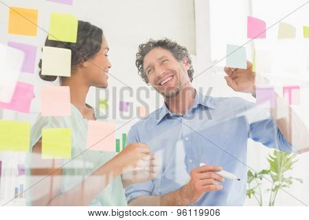 Puzzled business team lookingat notes  on the wall in the office