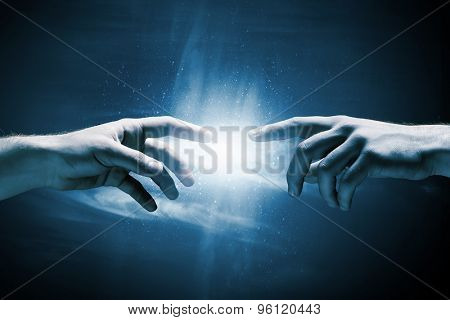Close up of two hands reaching each other with fingers