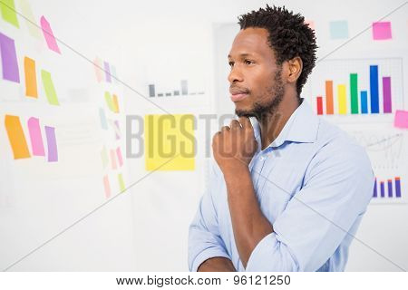 Young serious businessman looking at sticky notes in the office