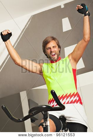 Young happy man in a jim spinning a cycle, victory sign- arms up, smiling excited.