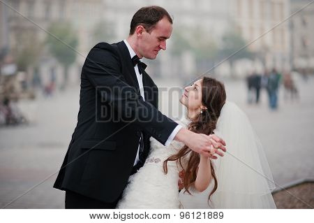 Young Elegant And Hearty Wedding Couple In Love On Streets Of Krakow, Poland