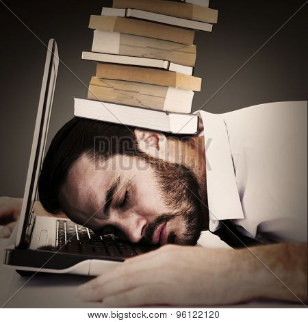 Businessman resting head on laptop keyboard against grey vignette