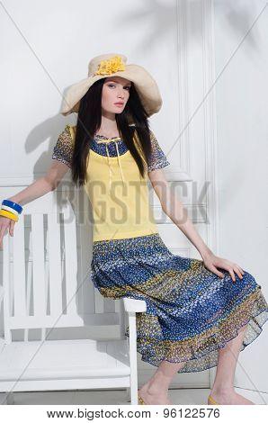 high fashion model in elegant dress sitting chair posing