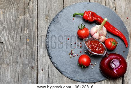 Ketchup Chili In A Glass Gravy Boat And Its Ingredients On A Black Tray