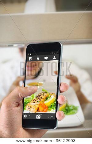hand holding smartphone against chef handing salmon dinner through order station