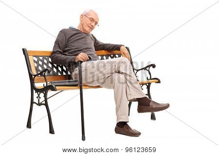 Studio shot of an old man with cane sleeping on a wooden bench with a book beside him isolated on white background