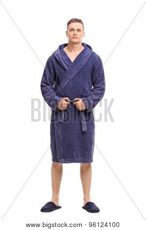 Full length portrait of a young man posing in a blue bathrobe isolated on white background