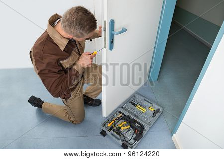 Carpenter Fixing Lock With Screwdriver