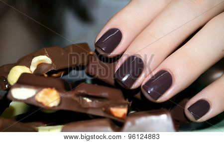 Beautiful woman hand with pieces of milk chocolate