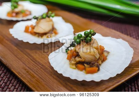 Seared scallops  served on a bed of vegetables on a scallop shell.