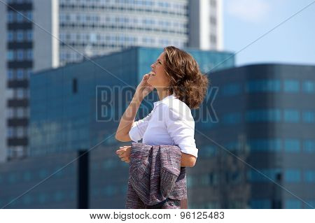 Business Woman Walking And Talking On Cell Phone In The City