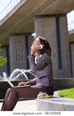 Business Woman With Mobile Phone And Laptop In City Park