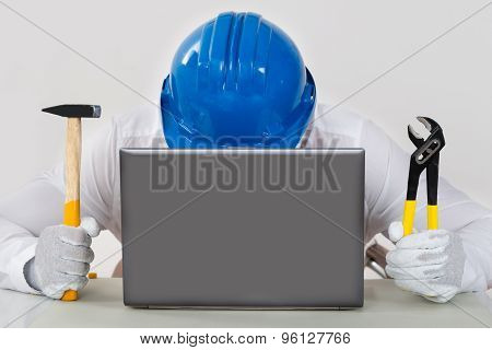 Technician Holding Hammer And Plier With Laptop