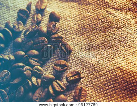 Coffee beans on burlap sack.Filtered image: cool cross processed vintage effect.