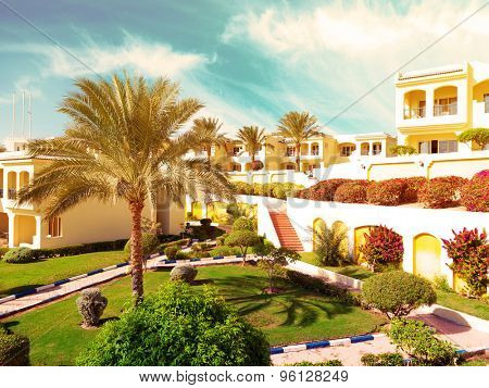 Palms and bungalow in hotel in Sharm el Sheikh, Egypt. Filtered image: warm cross processed vintage effect.