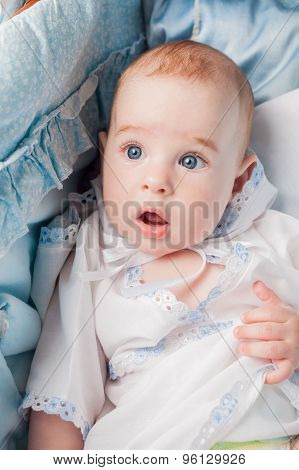 Surprised little boy laying in bed
