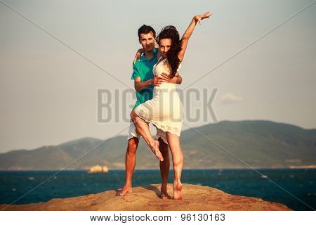 Girl And Guy Play Against Mountains