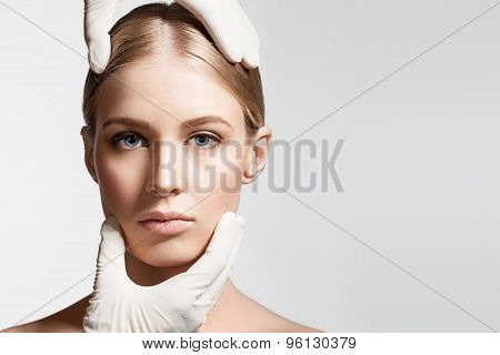 Hands in medical gloves holding the girl's head