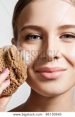 The smiling woman washes face foam and sponge