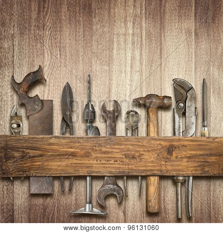 Old rusty tools under wooden plank.